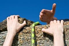 Escalador de roca que alcanza para el socio de la ayudar-mano. Imagen de archivo libre de regalías