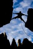 Escalador de roca que alcanza a través de una sima. Imágenes de archivo libres de regalías