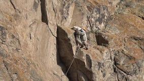 Escalador de roca que lucha para hacer movimiento difícil mientras que sube la pared de la roca almacen de video