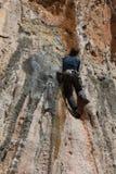 Escalador de roca que se aferra en un acantilado imagenes de archivo