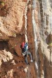 Escalador de roca que se aferra en un acantilado imagen de archivo
