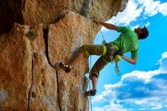 Escalador de roca que sube para arriba un acantilado Foto de archivo libre de regalías