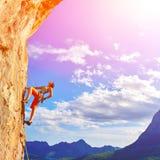 Escalador de roca que sube para arriba un acantilado Fotografía de archivo libre de regalías