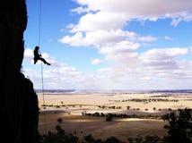 Escalador de roca rappelling Imagen de archivo libre de regalías