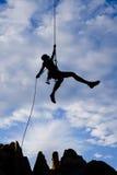 Escalador de roca rappelling. Imagen de archivo