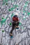 Escalador del muchacho en una pared Fotografía de archivo
