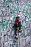 Escalador del muchacho en una pared Imágenes de archivo libres de regalías