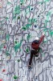 Escalador del muchacho en una pared Imagen de archivo libre de regalías