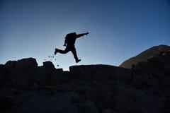 Escalador dinámico de la cumbre en las rocas Fotos de archivo libres de regalías
