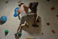 Escalador en el entrenamiento que intenta una trayectoria difícil Imagenes de archivo