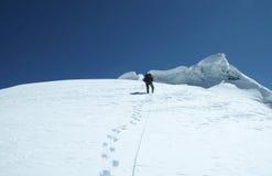 Escalador en el pico Fotografía de archivo