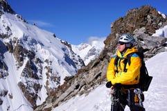 Escalador en el top de la montaña Fotos de archivo