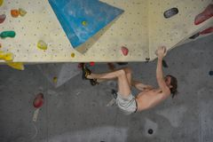 Escalador en la acción, colgando para arriba el lado abajo Imagen de archivo libre de regalías