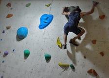 Escalador en la acción, concentración antes de un salto difícil Foto de archivo