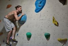 Escalador en la acción, concentración antes de un salto difícil Fotos de archivo