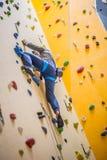 Escalador en la pared Escalada practicante del hombre joven en una roca wal Fotografía de archivo