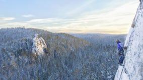 Escalador en una roca en la Siberia distante Foto de archivo