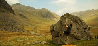 Escalador en una roca para hacer Bouldering en el distrito del lago, Reino Unido imagen de archivo