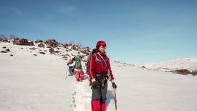 Escalador en una situación caliente roja del traje en la nieve con una selección de hielo en su mano y miradas en la distancia de metrajes