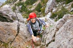 Escalador femenino alegre que asciende una roca Foto de archivo libre de regalías