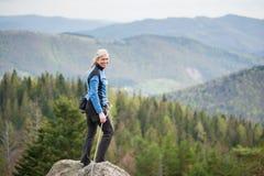 Escalador femenino en el pico de la roca con el equipo que sube Fotos de archivo