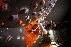 Escalador femenino fuerte en la pared que sube del canto rodado interior Fotografía de archivo libre de regalías