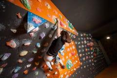 Escalador femenino fuerte en la pared que sube del canto rodado interior Imagen de archivo