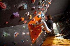 Escalador femenino fuerte en la pared que sube del canto rodado interior Fotos de archivo libres de regalías