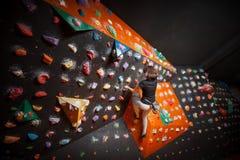 Escalador femenino fuerte en la pared que sube del canto rodado interior Imagenes de archivo