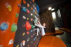 Escalador femenino fuerte en la pared que sube del canto rodado interior Foto de archivo