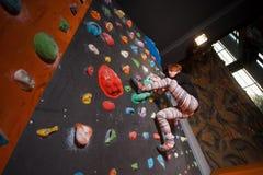 Escalador femenino fuerte en la pared que sube del canto rodado interior Fotos de archivo