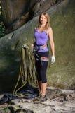 Escalador femenino que lleva a cabo la cuerda cerca del canto rodado grande Foto de archivo