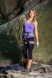 Escalador femenino que lleva a cabo la cuerda cerca del canto rodado grande Fotos de archivo libres de regalías