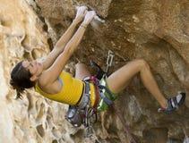 Escalador femenino que se aferra en un acantilado. Imagen de archivo libre de regalías