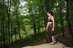 Escalador femenino que se coloca en el canto rodado natural grande en el bosque Imagen de archivo