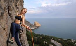 Escalador femenino que sube con la cuerda en una pared rocosa Imagen de archivo