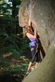 Escalador femenino que sube con la cuerda en una pared rocosa Fotografía de archivo