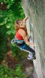 Escalador hermoso de la mujer que sube la roca escarpada con la cuerda Foto de archivo libre de regalías