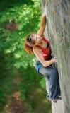 Escalador hermoso de la mujer que sube la roca escarpada con la cuerda Imagenes de archivo