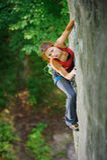 Escalador hermoso de la mujer que sube la roca escarpada con la cuerda Foto de archivo