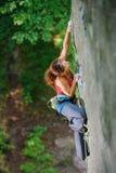 Escalador hermoso de la mujer que sube la roca escarpada con la cuerda Fotografía de archivo