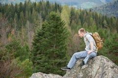 Escalador masculino con la mochila marrón en el pico de la roca Fotografía de archivo libre de regalías