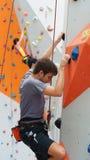 Escalador masculino de la pared en la reconstrucción de la acción Imagen de archivo libre de regalías
