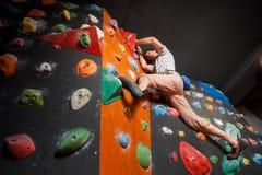 Escalador masculino fuerte en la pared que sube del canto rodado interior Fotografía de archivo libre de regalías