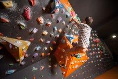 Escalador masculino fuerte en la pared que sube del canto rodado interior Imagen de archivo