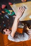 Escalador masculino fuerte en la pared que sube del canto rodado interior Foto de archivo libre de regalías