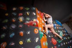 Escalador masculino fuerte en la pared que sube del canto rodado interior Foto de archivo