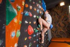 Escalador masculino fuerte en la pared que sube del canto rodado interior Imagen de archivo libre de regalías