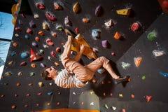 Escalador masculino fuerte en la pared que sube del canto rodado interior Fotos de archivo libres de regalías