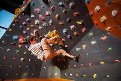 Escalador masculino fuerte en la pared que sube del canto rodado interior Imágenes de archivo libres de regalías